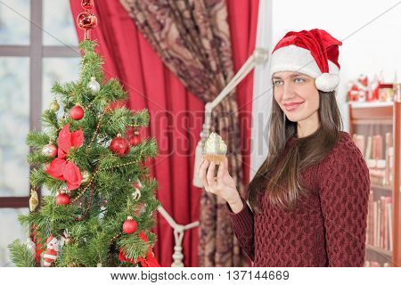 Half-length portrait of woman in burgundy sweater holding piece of tasty chocolate cake and smiling. Christmas interior with tree on background