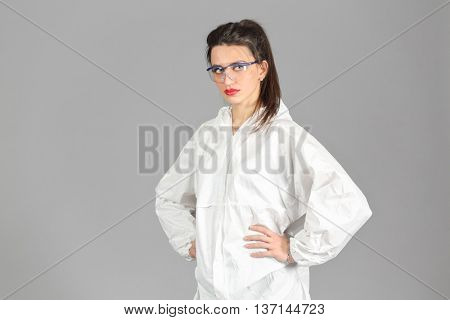 Half-growth portrait of woman in white protective suit of synthetic paper, looking at us, hands on waist, on gray background