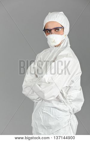 Half-growth portrait of woman in white protective suit of synthetic paper and respiritory half mask, looking at us, hands in lock on chest, on gray background