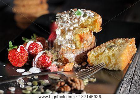 Fruitcake with yogurt and strawberries on a black plate