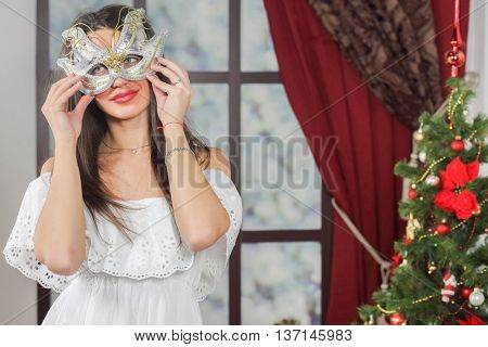 Half-length portrait of young woman in carnival mask standing near christmas three, looking away. Christmas interior studio