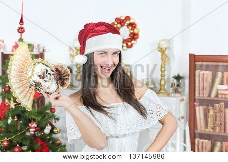 Half-length portrait of woman near Christmas tree. Girl in white dress and Santa hat with carnival mask in hand smile and look at us.