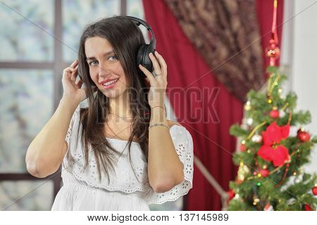 Half-length portrait of young woman standing near christmas three and listening music in headphone, smiling and look at us. Christmas interior studio, close-up