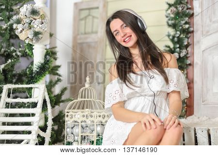 portrait of young woman sitting on threshold of fake home and listening music in headphone, smiling and look at us. Christmas interior studio, close-up