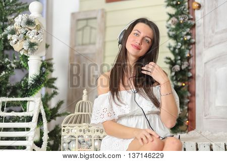 portrait of young woman sitting on threshold of fake home and listening music in headphone, smiling and look throw. Christmas interior studio, close-up