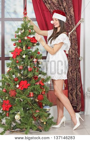 Full body portrait of woman near Christmas tree. Girl in white dress and Santa hat dresses up Christmas tree.