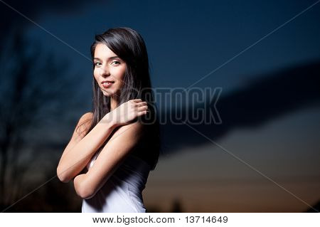 A Portrait Of A Young Woman At Sunset, With Her Arms Around Her Shoulders, Smiling.