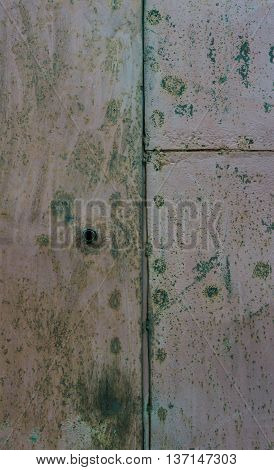 part of the gray rusty scratched metal gate covered with dark green stains it is visually divided into three parts, a hole for a key
