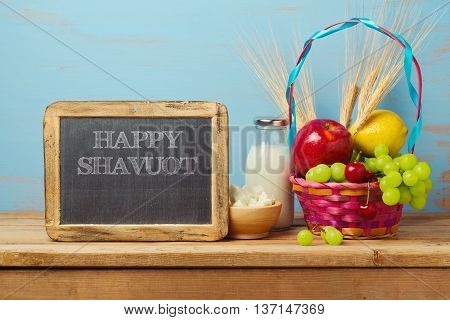 Happy Shavuot greeting design with milk and fruits basket on wooden table.