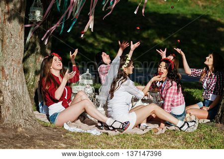 Happy And Sexy Girls Sitting At Picnic Table And Eating Strawberries On Bachelorette Party