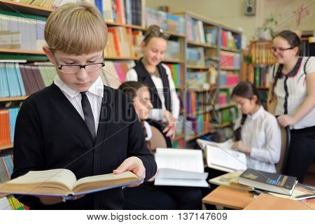 student in black jacket and glasses on background of shelves with books and other students, read book, shallow dof