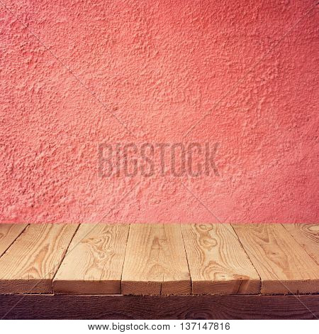 Empty wooden table over old red wall background