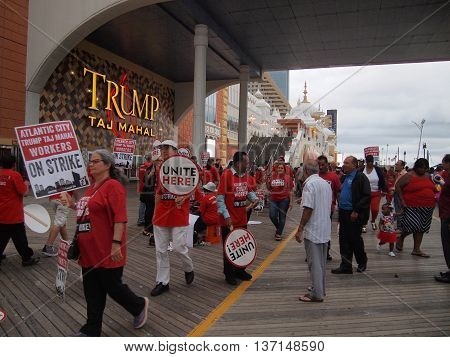 ATLANTIC CITY NJ - JULY 4: Workers strike marching in pickets lines and holding signs outside the Trump Taj Mahal casino on the boardwalk on July 4 2016 in Atlantic City New Jersey.