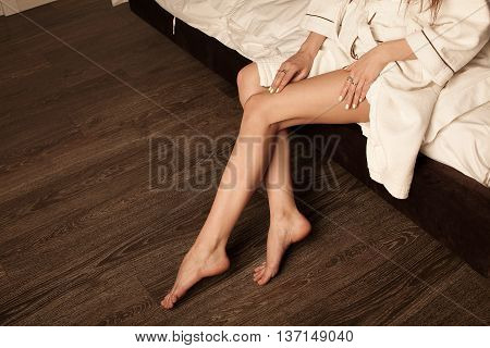 Attractive sexy woman leg in bathrobe in her bedroom.