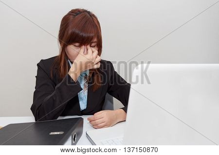Businesswoman touching her eyes with eyes pain office syndrome.