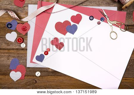 Scrapbooking background with craft paper, ribbon, buttons and heart cutouts. Space for your text.