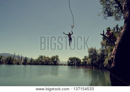 Photo of a man jumping to a river
