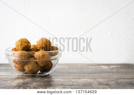 Vegetarian falafels on rustic wooden table and white wall