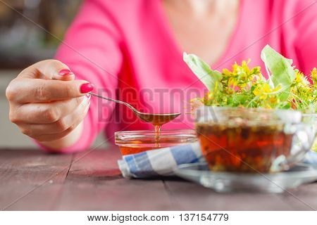 Woman Have Scooped The Spoon Of Honey On Wooden Table