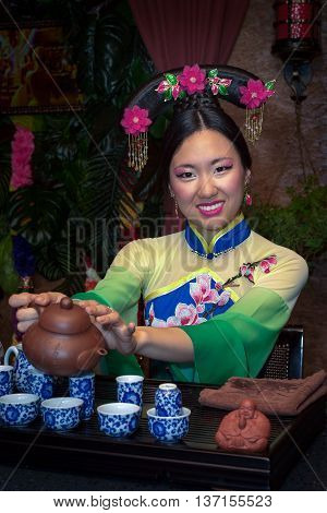 Beautiful Chinese Woman In A Tradition Clothes Pouring Tea During Tea Ceremony