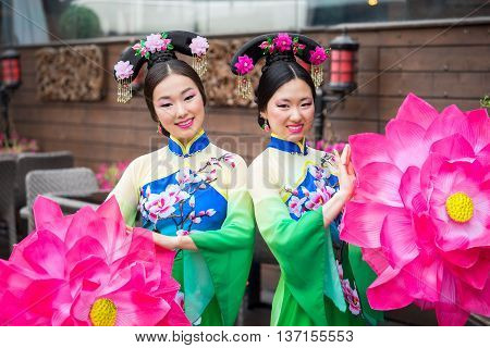 Two Beautiful Asian Girls In Traditional Chinese Blue And Green Dresses With Umbrella In A Form Of L