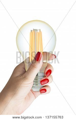 LED filament light bulb in female hand. Isolated on white background.