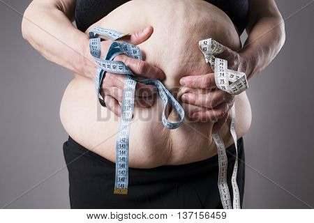 Obesity female body fat woman with measuring tape on gray background