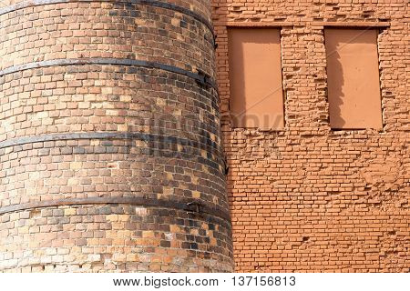 big old chimney closeup and part of a brick wall with niches for windows and blank space