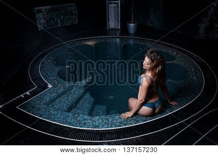 Beautiful young blonde caucasian woman in bikini relaxing in hot pool or jacuzzi at spa center water treatment and body care concept
