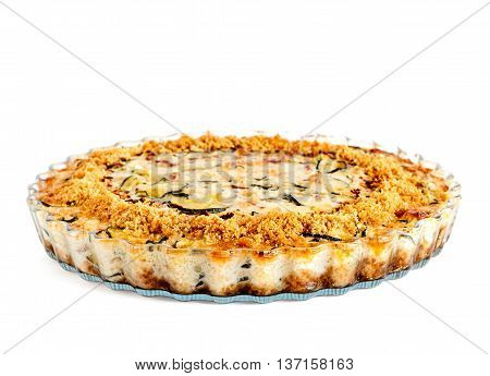 Lateral view of homemade crustless zucchini quiche baked in a glass fluted dish isolated on white