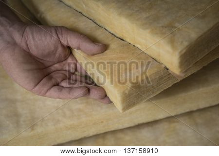 Hand holding a fiberglass batt. Image of home insulation.