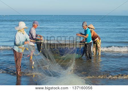 DA NANG, VIETNAM - JANUARY 04, 2016: Fishermen untangle a network, ready to go to sea for fishing