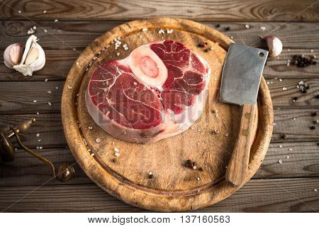 Raw fresh cross cut veal with garlic, pepper and seasonings on wooden cutting board with butcher cleaver. Eye bird view.