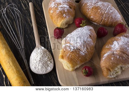 fresh croissant with flour, strawberry and handle mixer on wooden background.
