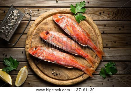 Fresh fish red mullet with lemon and seasonings on an cutting board Top view