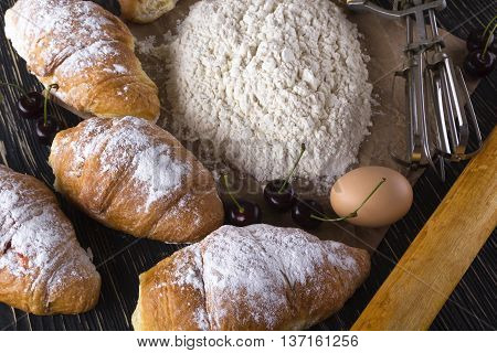 fresh croissant with flour, cherry, handle mixer and eggs on wooden background.