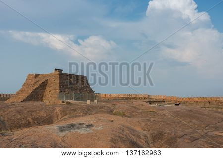 Chettinad India - October 16 2013: A pyramid with cannon stands on top of plateau at the Thirumayam fort. The rampart and battlements form a line under blue skies.