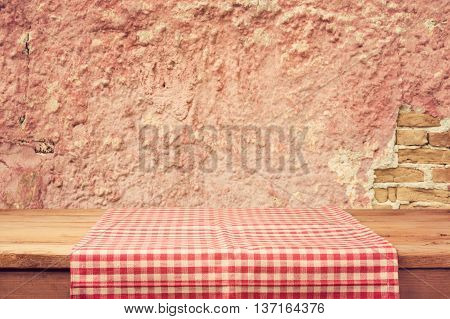 Empty wooden deck table with tablecloth over vintage wall background