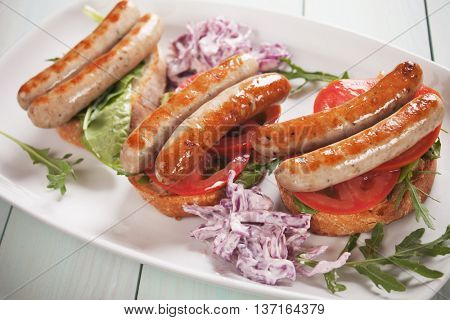 Grilled sausage sandwich with tomato, rocket salad and coleslaw