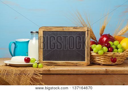 Chalkboard with fruit basket and milk on wooden table. Jewish holiday Shavuot background with place for text