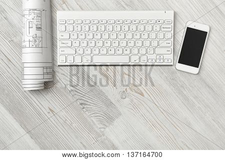Workplace with architectural drawings, keyboard and smarthphone in top view. Conducive working environment. Engineering work. Construction and architecture.