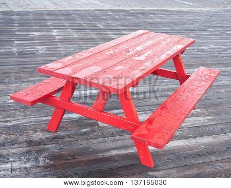 Wet picnic table on boardwalk after rainfall.