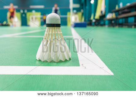 White badminton shuttlecock on a green floor with blurred players in badminton court.