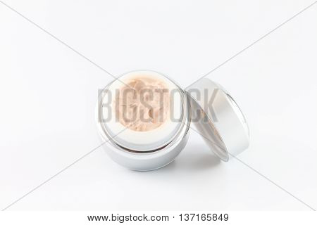 Open jar of cosmetic face cream on white background