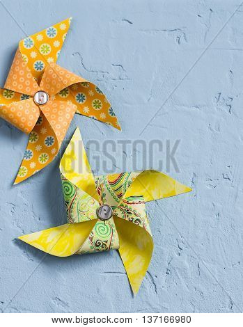 Two homemade paper pinwheel on a blue stone background. Free space for text