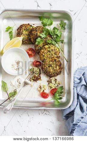 Zucchini quinoa fritters. Delicious healthy vegetarian food. On a light background top view