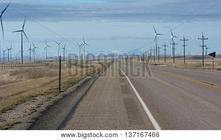 A straight road splits a field of spinning wind turbines.