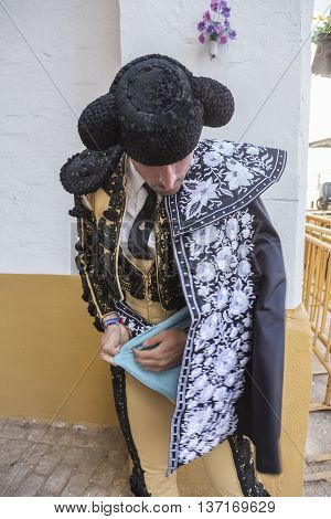 Linares SPAIN - August 29 2014: Spainish bullfighter putting itself the walk cape in the alley before going out to bullfight typical and very ancient tradition in Linares Jaen province Spain