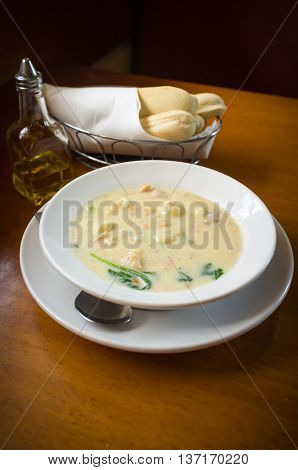 Creamy chicken gnocchi traditional Italian soup with bread and oilve oil