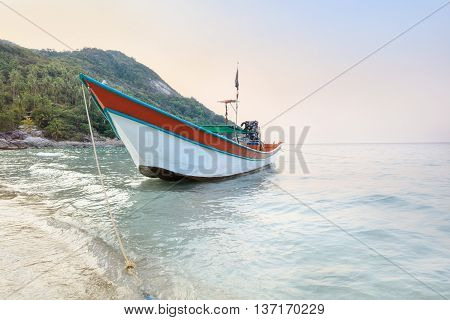White long tail boat on tropical beach at sunset
